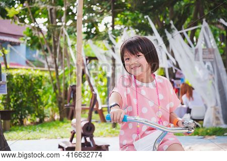 Cute Asian Girl Riding Bicycle. Sweet Smile Child Looking At Camera. Happy Kid Wearing Pink Clothes.