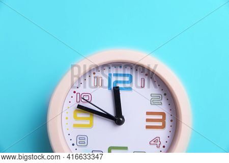 A Round Clock Is On A Blue Background. Copy Space. Ten To Twelve