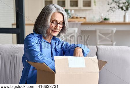 Happy Senior Middle 60s Aged Woman Opening Box With Ordered Clothes At Home On Couch. Old Mature Onl