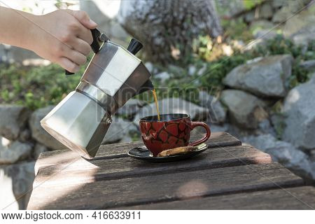 Female Hand Holds Iron Geyser Coffee Maker And Pouring Hot Coffee In Cup Outside On Old Wooden Table