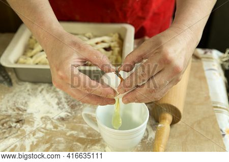 Mom's Pies. Mom Prepares A Mixture Of Eggs To Grease The Cake Before Baking. Cooking During Quaranti