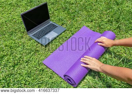 Female Hands Spread The Yoga Mat On The Green Grass. Online Sports Training In The Garden.