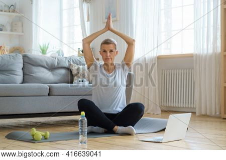 Senior Woman With Closed Eyes, Online Training In Living Room. Exercising With Laptop Watching Fitne