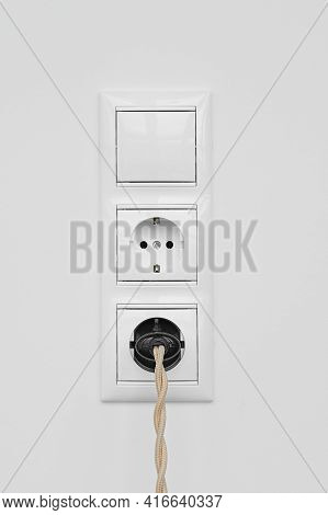 Block Of Two White Plastic Electrical Outlets And Switch Isolated On White Plastered Wall. Electrica