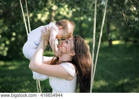 Happy Childhood Of A Healthy Child. Close-up Baby In Mother's Arms. Mom Pressed Against The Forehead