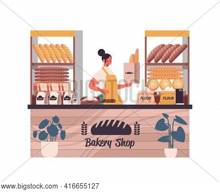 Female Baker Holding Bag With Baguettes Woman In Uniform Selling Fresh Bakery Products In Baking Sho