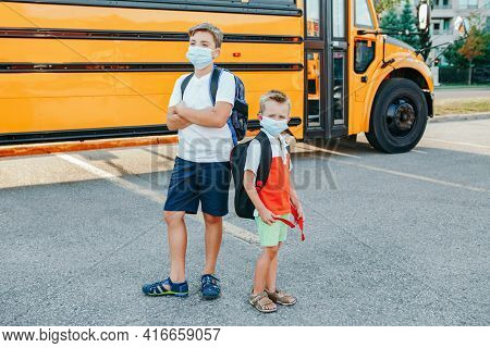 Brothers Students In Face Masks Standing By Yellow School Bus Outdoor. Kids With Personal Protective