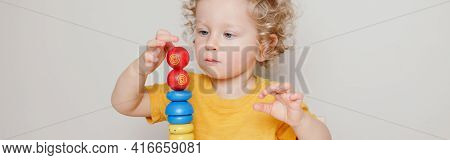 Cute Baby Toddler Playing With Learning Toy Pyramid Stacking Blocks At Home, Kindergarten. Early Age
