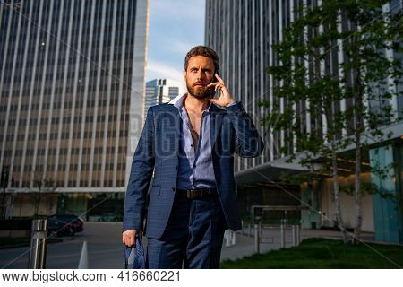 Businessman Walking In City. Business Man Using Mobile Phone Outside Of Office In Urban City With Sk