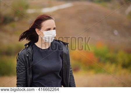 Young Woman In Medical Mask Standing In Countryside. Adult Brunette In Protective Mask In Cool Weath