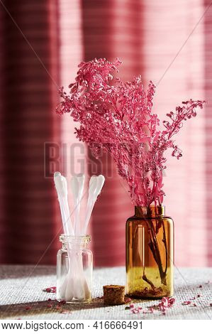 Jar With Cotton Buds And Cosmetic Bottles On The Makeup Desk With A Flowers. Fashion And Bodycare Co