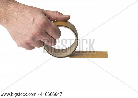 A Man's Hand Unwinds An Adhesive Tape Isolated On A White Background. Universal Packaging Tape.