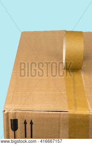 Packaging Of A Large Cardboard Box With Adhesive Tape On A Blue Background. Universal Packaging Tape
