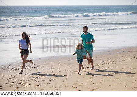 Happy Family Running Out The Water In Beach. Summer Vacations And Sporty Healthy Family. Active Pare