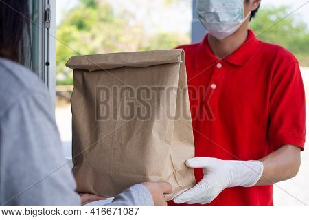 A Courier Wearing A Red Uniform With Gloves And Face Masks To Prevent The Risk Of Contamination In D