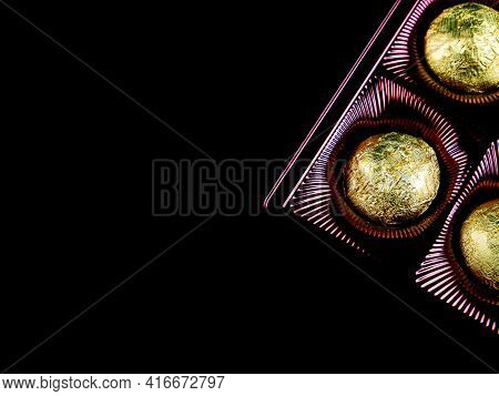 A Box Of Chocolates In A Golden Foil Wrapper On A Black Background. Sweets In Shiny Foil. Golden Col