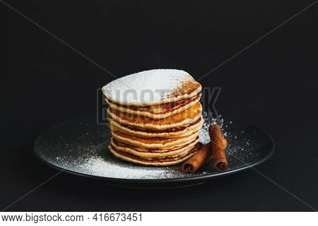Stack Of Pancakes With Sugar Powder And Cinnamon. On A Dark Background. Copy Space For Your Text.