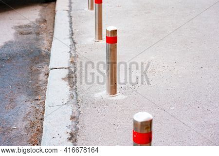 Stainless Bollards With Red Reflective Strip On The Top Installed On The Pavement To Block Cars From