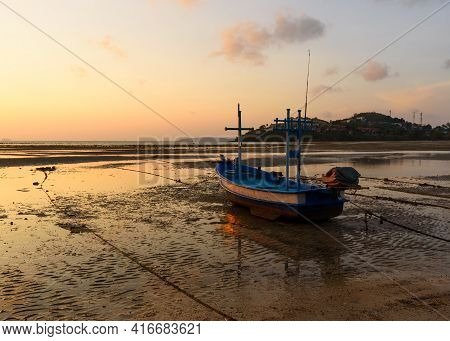 A Longtail Boat On The Beach During Low Tide At Phuket Province. Background Of Morning Sunlight And