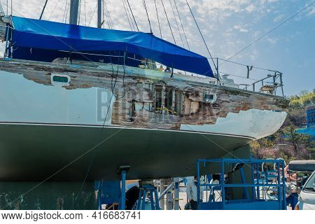 Sailboat In Dry Dock For Repair With Hole In Side Hull.