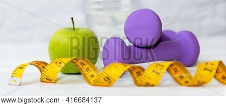 Select Focus And Close Up Dumbbells.  Diet Health Plan.  Green Apple With Measure Tape For Nutrition