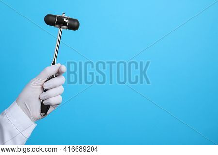 Doctor Holding Reflex Hammer On Light Blue Background, Closeup With Space For Text. Nervous System D