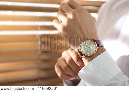 Man With Luxury Wrist Watch On Blurred Background, Closeup. Space For Text