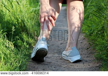 Ankle Sprain, Woman Grabbed Her Leg While Walking On A Spring Or Summer Nature. Concept Of Tired Leg
