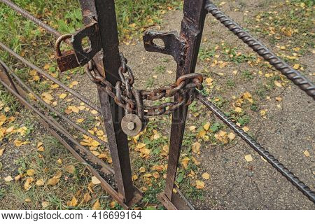 A Rusty Bolt Lock On An Old Rusty Chain On An Iron Gate. Left Space Concept Or Abandoned Area. Soft