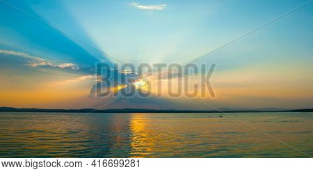 Sea sunset,sea landscape,sea water surface lit by sunset summer light,panorama of the sea.Sea summer nature with mountain range at the horizon,sea nature, sea water, sea vacation,sea travel, sea landscape