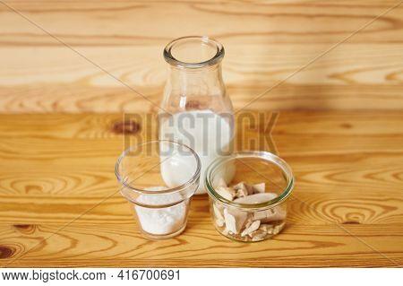 Dough Starter Ingredients In Transparent Glasses On Brown Wooden Background. Fresh Wild Yeast, Milk