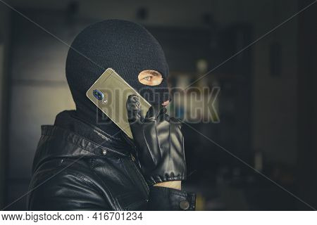 Young Adult In Black Clothes With Hidden Face. Ill-intended Fraudster Uses Mobile. Fraudster Calls.