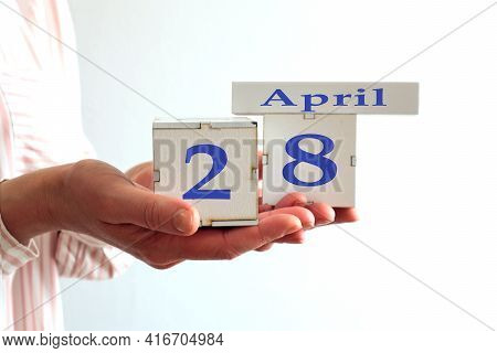 Calendar For April 28 : Women's Hands Hold Cubes With The Number 28, The Name Of The Month Of April