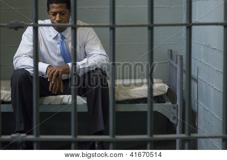 Depressed businessman sitting on bed behind a prison gate