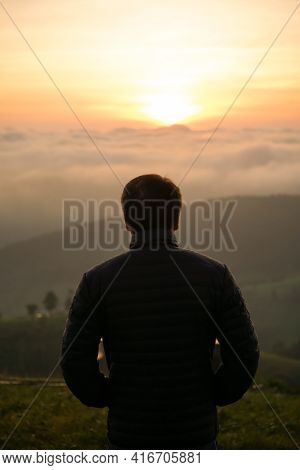 Man Watching Sunrise Alone At Hilltop With Mist