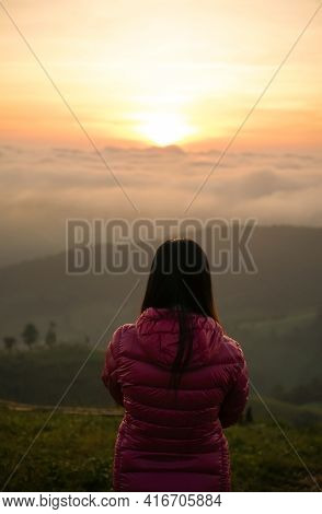 Woman Watching Sunrise Alone At Hilltop With Mist
