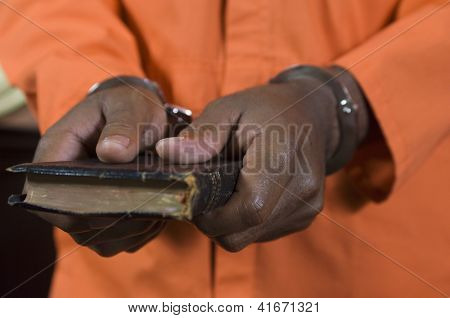 Close up of criminal's hand in handcuffs taking oath