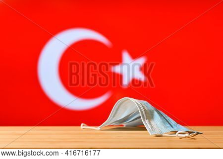 The Medical Mask Lies On The Table Against The Background Of The Flag Of Turkey. The Concept Of A Ma