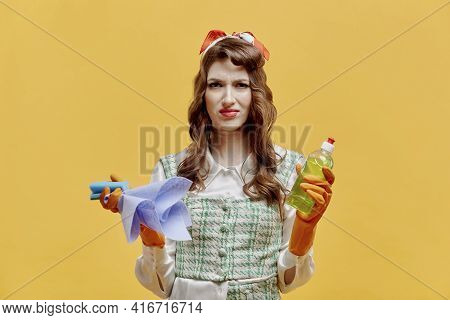 A Disgruntled Female Cleaner With Tools For Cleaning The House. Pin-up Style.