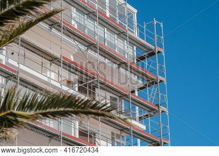 Renovation Of The Facade Of A Hotel In A European Resort On Palm Trees And Blue Sky Background. Buil