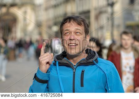 Street Portrait Of A 45-50-year-old Man Looking Up And Pointing At Something, Urban Background, Medi