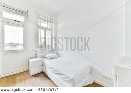 Comfortable Bed With White Bedclothes And Bedside Table With Lamp Placed Near Window And Balcony Doo