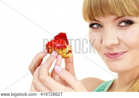Woman Holds Cake Cupcake In Hand Taking A Huge Bite Out Of Dessert, Eating Unhealthy Junk Food. Swee