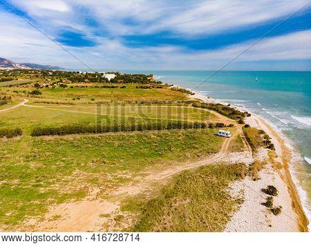 Aerial View. Coastal Landscape With Caravan Wild Camping On Beach Sea Shore. Mediterranean Coast Of