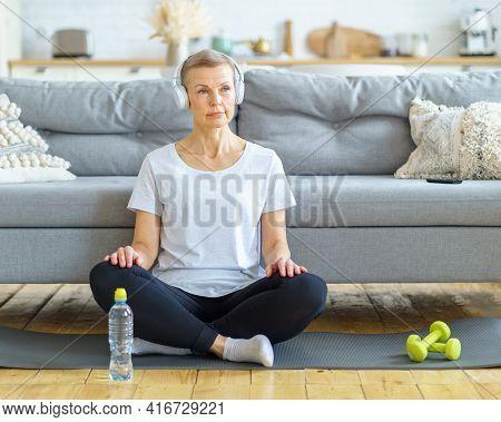 Senior Woman Sit Cross-legged In Headphones Listen Music In Living Room. Relax After Exercising Fitn
