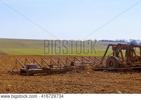 A Farmer Plows The Soil In The Field With A Chisel Plow On A Tractor. Agricultural Tractor With A Pl