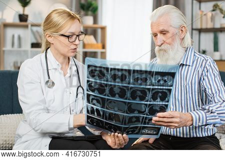 Geriatric Care, Home Visit. Pretty Confident Female Healthcare Worker Discussing The Results Of X-ra