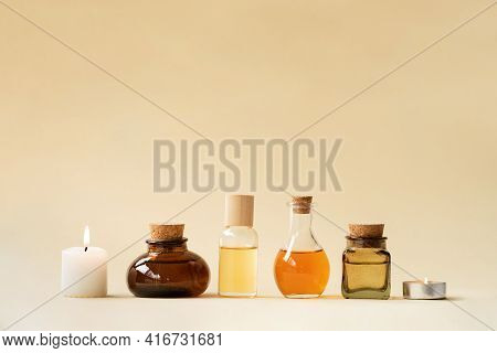 Concise Spa Composition With Oil Flasks And Candles On Beige Background.
