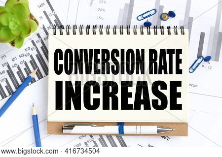Conversion Rate Increase. Text On White Notepad Paper On Light Background Next To Financial Charts