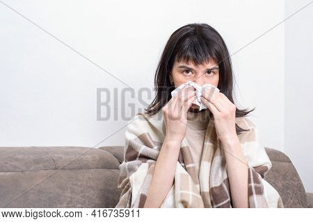 Sick Day At Home. Sick Woman Sitting On Sofa Holding Paper Handkerchief Blowing Her Nose Feels Unhea